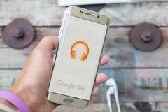 Une main d'homme tenant la copie d'écran de la musique de jeu de Google sur le bord de la galaxie s6 de Samsung photographie stock libre de droits