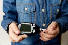 Une main de garçon tenant Glucometer pour l'essai de glucose sanguin sur la table en bois, les soins de santé et la technologie m Photos stock
