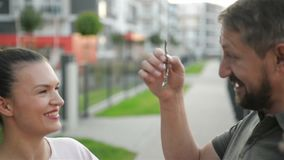 Une main des propriétaires masculins de Gives Keys To d'agent de Real Estate de la nouvelle maison Couples heureux clips vidéos