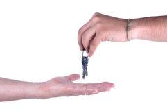 Une main donnant des clés à autre d'isolement Photos libres de droits