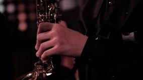 Une main du ` s d'homme dans un costume noir sur un saxophone Longueur sur un thème musical banque de vidéos