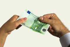 Une main du ` s d'homme et une main du ` s de femme tiennent cent factures d'euro Image libre de droits