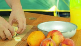 Une main du ` s de femme écarte les morceaux d'une banane dans une salade banque de vidéos
