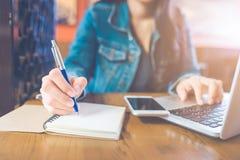Une main du ` s de femme écrit sur un bloc-notes avec un stylo et des WI d'un téléphone photos stock