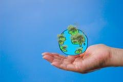 Une main du ` s de femme avec un globe créé d'une peinture avec un arbre dans la forêt Image libre de droits