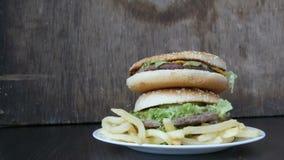Une main du ` s de femme prend un hamburger d'une grande montagne de trois hamburgers juteux délicieux avec les feuilles et le fr clips vidéos