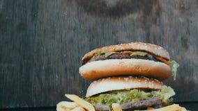 Une main du ` s de femme prend un hamburger d'une grande montagne de trois hamburgers juteux délicieux avec les feuilles et le fr banque de vidéos