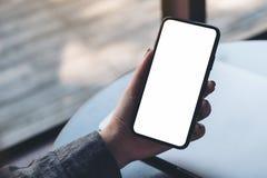 Une main du ` s de femme tenant le téléphone portable noir avec l'écran de bureau blanc vide avec l'ordinateur portable sur la ta Image libre de droits