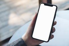 Une main du ` s de femme tenant le téléphone portable noir avec l'écran de bureau blanc vide avec l'ordinateur portable sur la ta Photos libres de droits