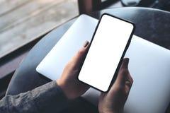 Une main du ` s de femme tenant le téléphone portable noir avec l'écran de bureau blanc vide avec l'ordinateur portable sur la ta Photographie stock libre de droits