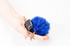Une main du ` s de femme tient des clés de voiture et la porte électronique ouvrent Image stock