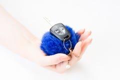 Une main du ` s de femme tient des clés de voiture et la porte électronique ouvrent Images libres de droits