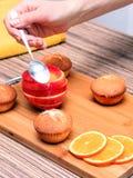 une main femelle arrose les petits pains cuits de maisons avec du sucre en poudre sur une table en bois, après une orange et une  Photographie stock libre de droits