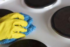Une main femelle dans un gant jaune lave le fourneau électrique avec du chiffon photos libres de droits