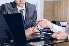 Une main femelle montre quelque chose sur l'écran d'ordinateur à un homme d'affaires photos libres de droits