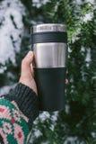 Une main i tenant une tasse thermo réutilisable, thermos, tasse de voyage sur le fond d'un arbre conifére couvert de neige, hiver image libre de droits
