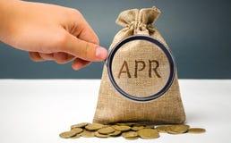Une main indique un sac d'argent avec le mot avr. C'est des honoraires financiers, a exprimé comme taux annuel Applicable pour pr photos stock