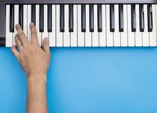 Une main jouant des clés sur le clavier de musique avec le bleu Photo libre de droits