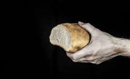 Une main jugeant une miche de pain d'isolement sur le noir Image stock