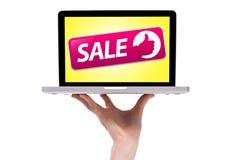 Une main mâle retenant un ordinateur portatif avec le signe de vente Photo libre de droits