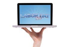 Une main mâle retenant un ordinateur portatif avec un signe de Fête du travail Photographie stock libre de droits