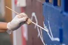 Une main peint la couleur sur la porte de fer photos libres de droits