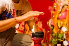 Une main prenant la chaleur de la flamme comme bénédiction d'une lampe allumée d'argile sur un diwali d'Inde de durgapuja d'idole image libre de droits