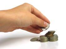 Une main prenant quelques pièces de monnaie image stock