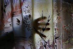 Une main rampante derrière un rideau La crainte du cambriolage ou des monstres photo libre de droits