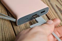 Une main relie un câble d'usb à une banque de puissance sur un fond en bois Batterie externe Photo stock