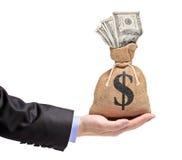 Une main retenant un sac d'argent avec le dollar US Photos libres de droits