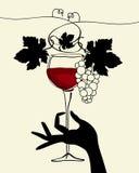 Une main retenant une glace de vin avec du raisin Photo libre de droits