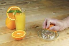 Une main serrant le jus d'une orange sur un presse-fruits en verre manuel Placez sur une table planked en bois images libres de droits