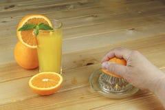 Une main serrant le jus d'une orange sur un presse-fruits en verre manuel Placez sur une table planked en bois image stock