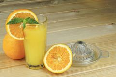 Une main serrant le jus d'une orange sur un presse-fruits en verre manuel Placez sur une table planked en bois image libre de droits