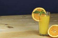 Une main serrant le jus d'une orange sur un presse-fruits en verre manuel Placez sur une table planked en bois photos libres de droits