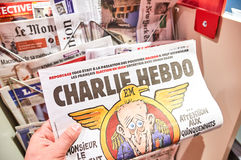 Une main tenant Charlie Hebdo Photographie stock