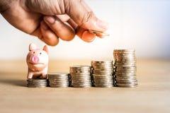 Une main tenant la pièce de monnaie sur enregistrer l'argent pour l'avenir avec la tirelire sur l'argent de pile, succès de la vi image stock