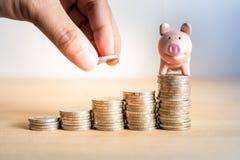 Une main tenant la pièce de monnaie sur enregistrer l'argent pour l'avenir avec la tirelire sur l'argent de pile, succès de la vi images libres de droits