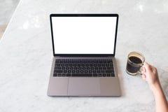 Une main tenant la tasse et l'ordinateur portable de café avec l'écran de bureau blanc vide sur la table de marbre en café Photographie stock libre de droits
