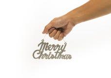 Une main tenant le signe argenté de Joyeux Noël Photos stock