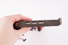 Une main tenant un conseil avec trois conectors d'USB Photo libre de droits