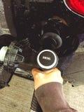 Une main tenant un gicleur d'essence et remplissant vers le haut d'une voiture de diesel image stock