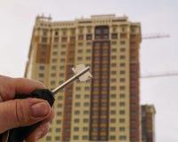 Une main tient les clés sur le nouvel appartement sur le fond du nouveau bâtiment Photos stock
