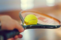 Une main tient une raquette de tennis dessus qui se trouve une boule jaune photo stock