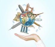 Une main tient un globe avec les endroits les plus célèbres au monde Un modèle des croix de bicyclette du globe Un concept du dép Image libre de droits