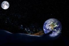 Une main tient un globe sur un fond des étoiles et de la lune image stock