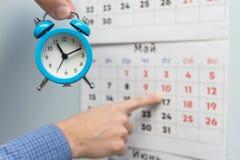 Une main tient un petit réveil, à l'arrière-plan des points d'une main sur de longs week-ends et vacances sur un calendrier mural image stock