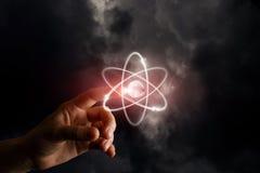Une main touche une sphère brillante avec les cercles brûlants autour au fond brumeux foncé Le concept est les nouvelles technolo photos stock