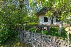Une maison avec le toit couvert de chaume blanc et blanchi de murs et les fenêtres ordonnées se tenant dans une cour sur une herb photographie stock